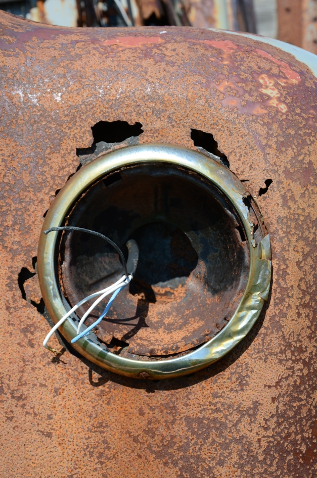 Missing headlight of a rusty old car