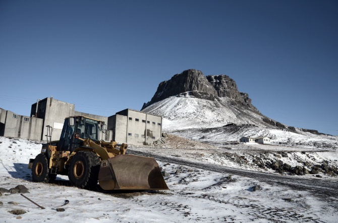 Earthmover with the mountain Þyrill and rhyolite factory in the background - partially desaturated